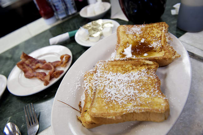 Close up of French toasts and bacon on restaurant table — Stock Photo