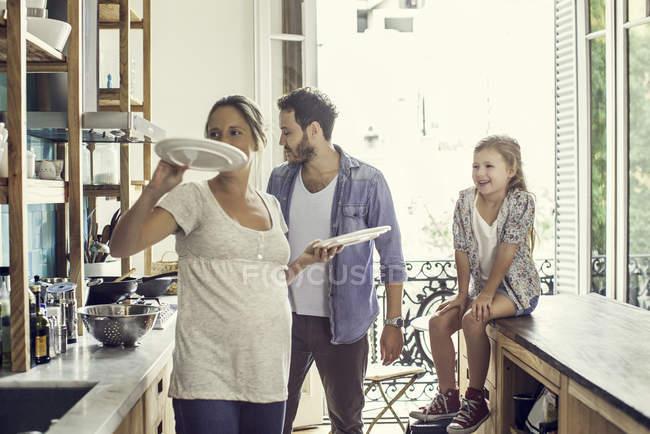 Ragazza a guardare come i genitori e preparare il pasto con la famiglia ta casa — Foto stock