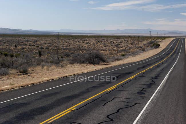 Autoroute vide à travers un paysage aride dans la journée — Photo de stock