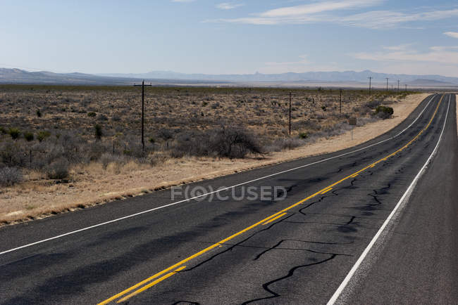 Empty Highway through arid landscape at daytime — Stock Photo