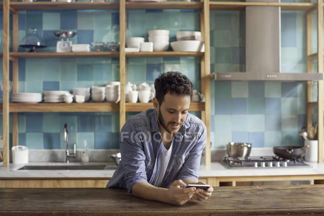 Uomo che usando smartphone alla cucina di casa — Foto stock