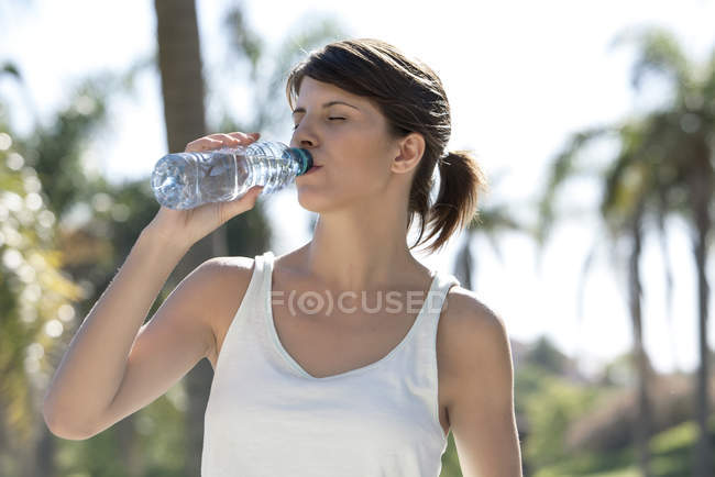 Woman drinking bottled water outdoors — Stock Photo