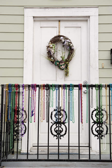Festive wreath and mardi gras beads on entrance to home — Stock Photo