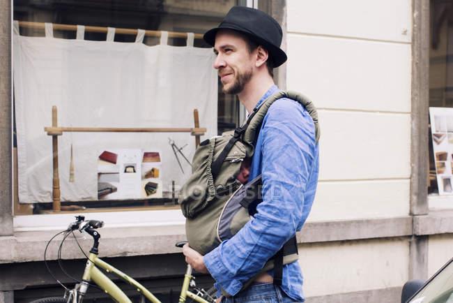 Homme dans la ville avec bébé dans le porte-bébé — Photo de stock