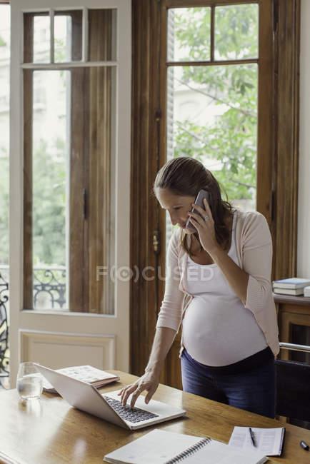 Женщина использует ноутбук и делает телефонный звонок — стоковое фото