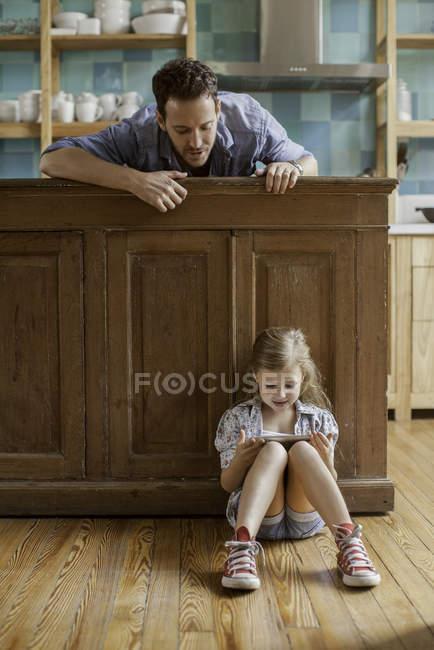 Отец смотрит на дочь, играющую в видеоигры — стоковое фото