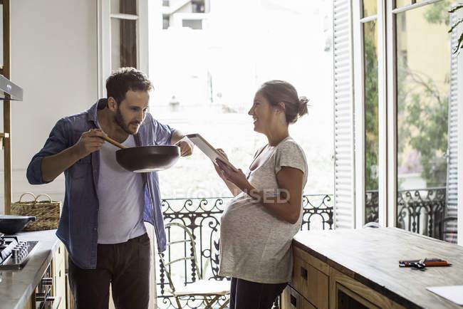 Esposo y esposa en casa cocinando juntos - foto de stock