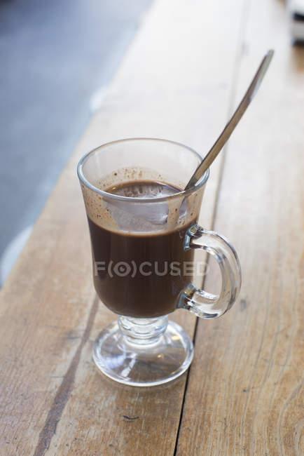 Primer plano de chocolate caliente en vidrio con cuchara - foto de stock