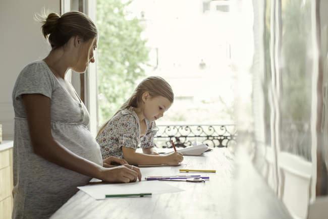 Mère regardant la coloration fille avec des conseils feutre à la maison — Photo de stock
