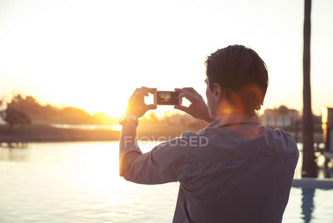 Man photographing sunset with smartphone — Stock Photo