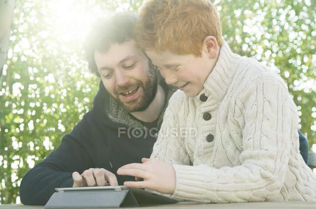 Отец и сын смотрят на цифровой планшет вместе — стоковое фото