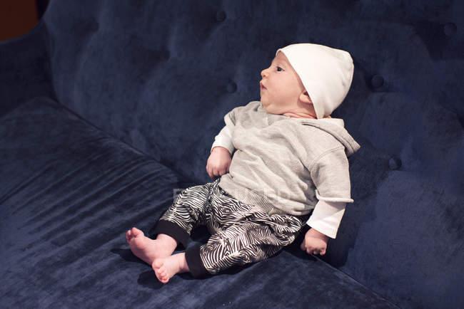 Retrato de niño pequeño sentado en el sofá - foto de stock