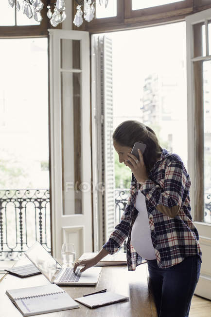 Pregnant woman working from home using laptop — Stock Photo