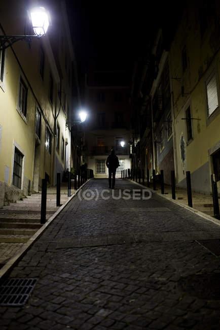 Homem andando na rua de paralelepípedos à noite — Fotografia de Stock