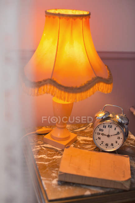 Lamp, alarm clock on bedside table — Stock Photo