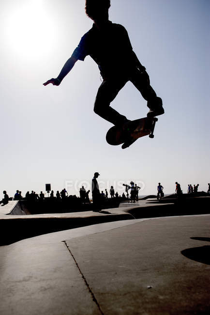 Skateboarder jumping in midair at skate park — Stock Photo