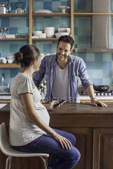 Embarazada esposa charlando con el marido en la cocina - foto de stock