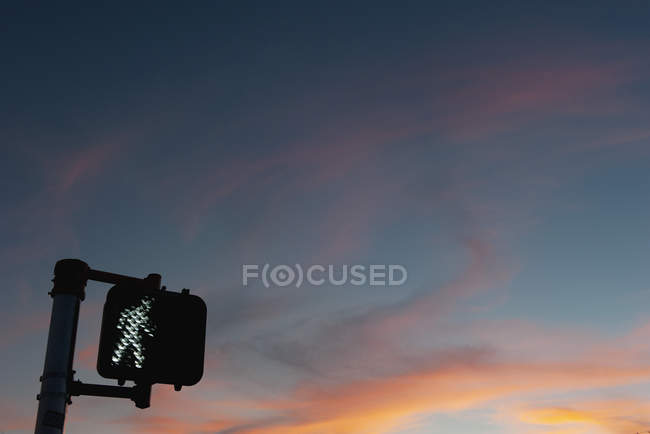 Walk signal with sunset in the background — Stock Photo