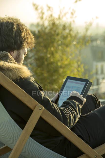 Uomo che per mezzo della compressa di digital all'aperto che si siede nella sdraio — Foto stock
