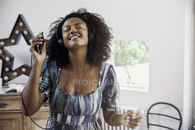Donna che balla durante l'ascolto di musica sullo smartphone — Foto stock