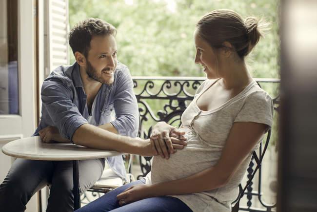 Чоловік спокою руку на дружини вагітна живіт — стокове фото
