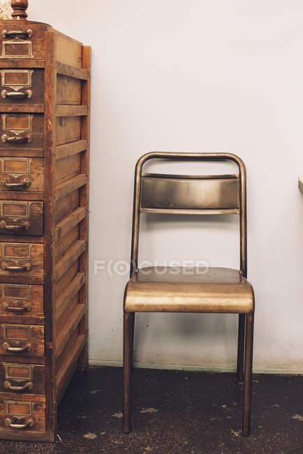 Chaise à côté de la vieille commode — Photo de stock