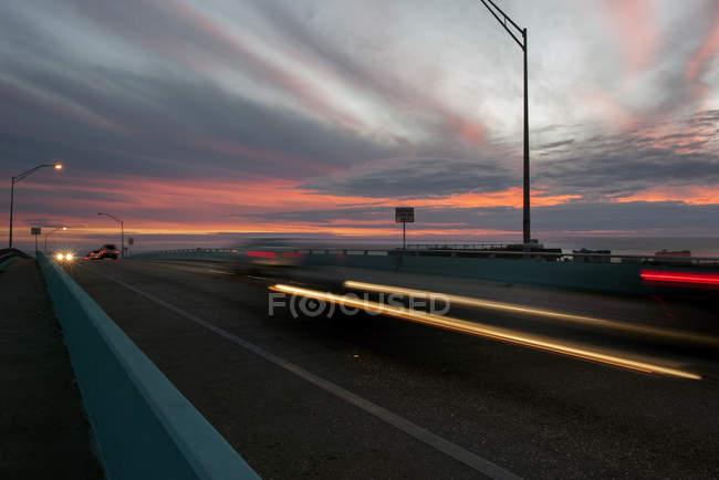 Легкие трассы от движения по шоссе на закате — стоковое фото