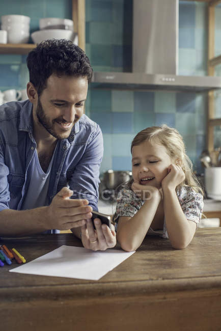 Father and daughter watching video streaming on smartphone together — Stock Photo