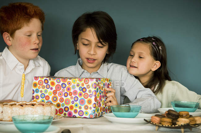 Children looking at wrapped gift at birthday party — Stock Photo