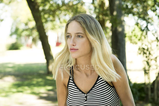 Portrait of young serious woman looking at away outdoors — Stock Photo