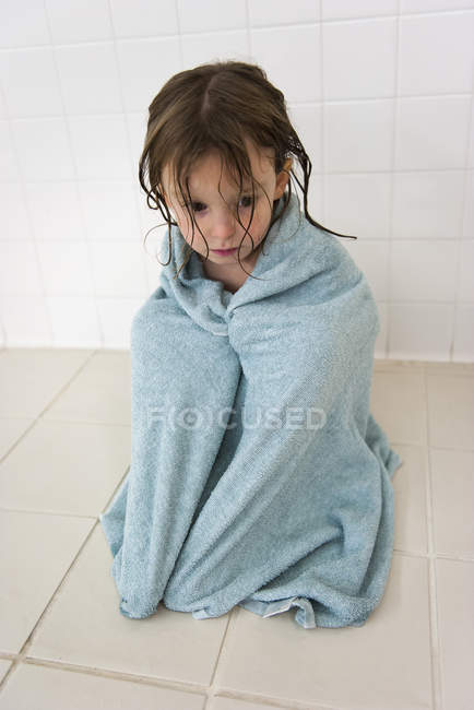 Маленькая девочка, завернутая в полотенце, печально смотрит вниз — стоковое фото