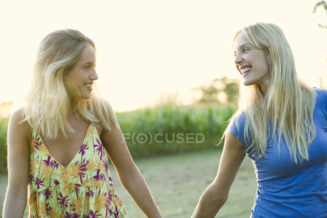 Female couple walking and holding hands outdoors — Stock Photo