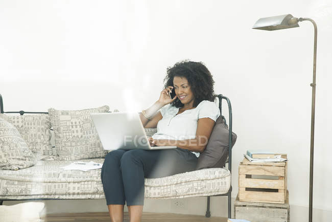 Woman chatting on cell phone and using laptop computer at home — Stock Photo