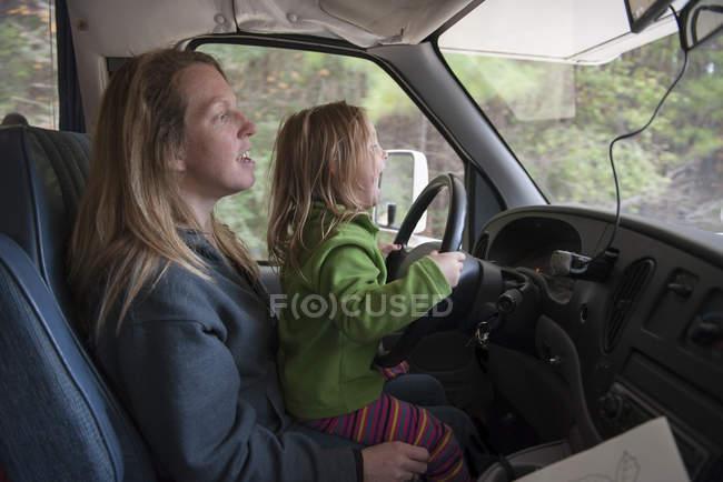 Kleines Mädchen sitzt auf Mutters Schoß hinter Lenkrad Auto — Stockfoto