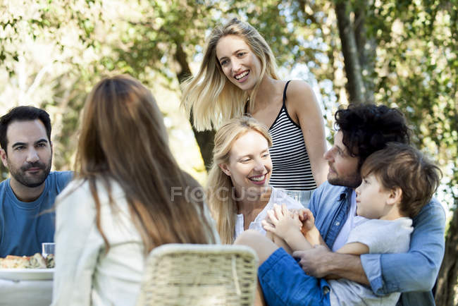 Friends and family enjoying meal together outdoors — Stock Photo