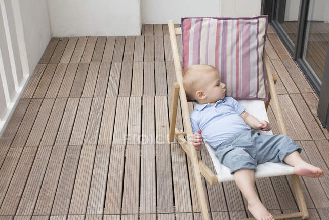 Baby reclining on lounge chair — Stock Photo