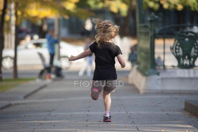 Visão traseira da menina correndo na calçada — Fotografia de Stock
