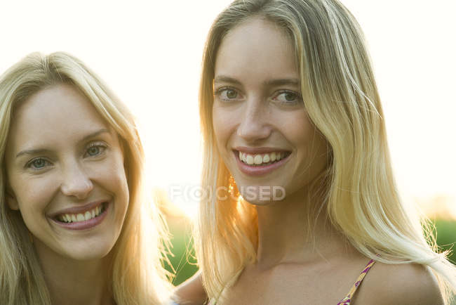 Portrait de deux femmes blondes souriant sur la caméra à l'extérieur — Photo de stock