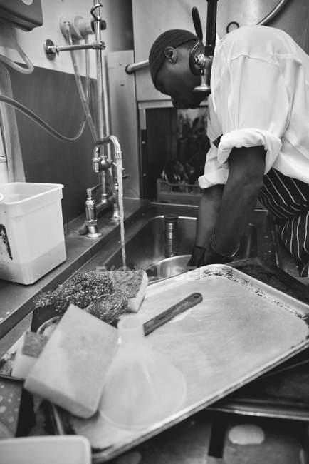 Arbeiter spült Geschirr in gewerblicher Küche — Stockfoto