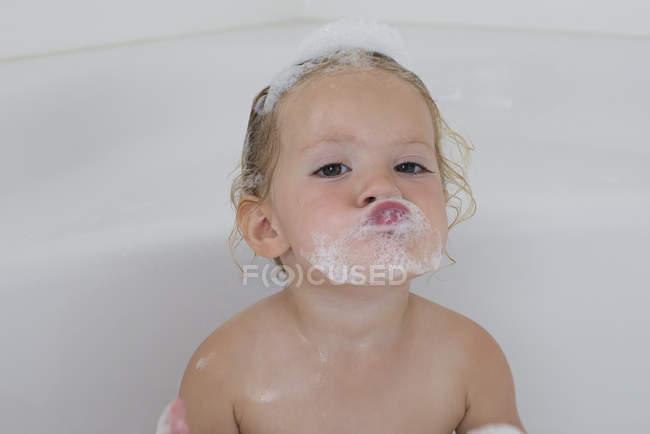 Portrait of funny little girl taking bath with foam — Stock Photo
