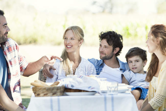 Extended family eating meal and talking together outdoors — Stock Photo