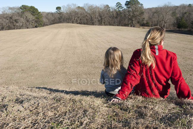 Rear view of Mother and daughter sitting together on hill — Stock Photo
