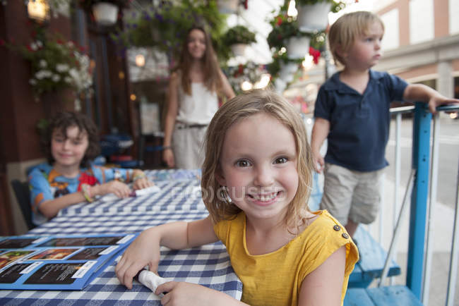 Portrait of Little girl sitting at outdoor cafe with brothers and mother — Stock Photo