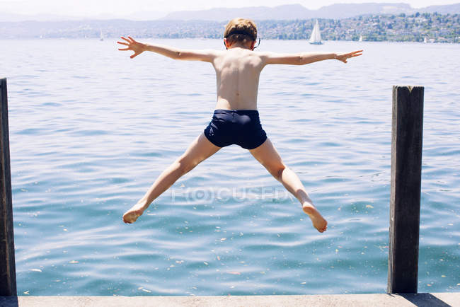Back view of boy jumping into lake — Stock Photo