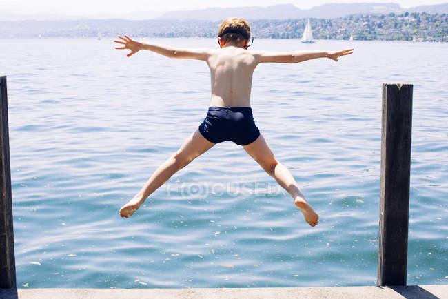 Vista do garoto pulando no lago traseira — Fotografia de Stock