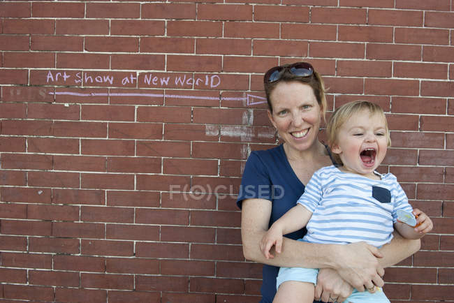 Portrait of mother and toddler son standing together against brick wall outdoors — Stock Photo