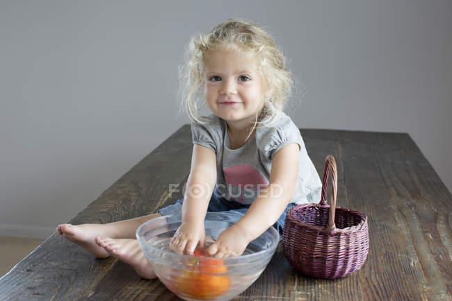 Девушка полоскает овощи в миску, сидя на деревянном столе — стоковое фото