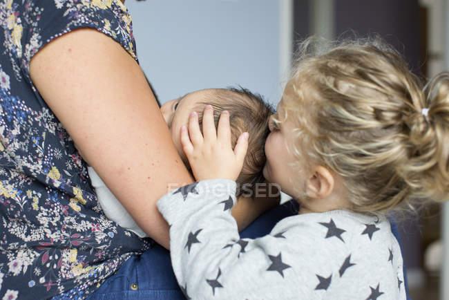 Mère avec bébé garçon et petite fille embrassant frère — Photo de stock