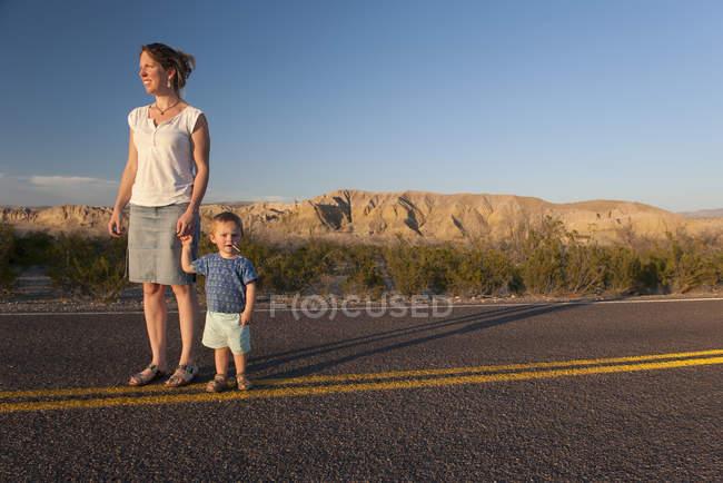 Figlio di madre e bambino che camminano insieme sulla strada ...
