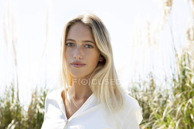 Portrait of young serious woman looking at the camera outdoors — Stock Photo